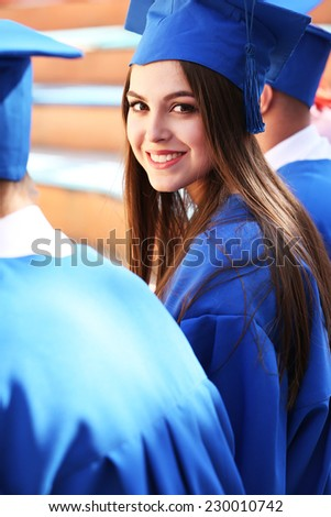 Graduate students wearing graduation hat and gown, outdoors - stock photo