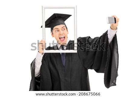 Graduate taking selfie behind a picture frame isolated on white background - stock photo