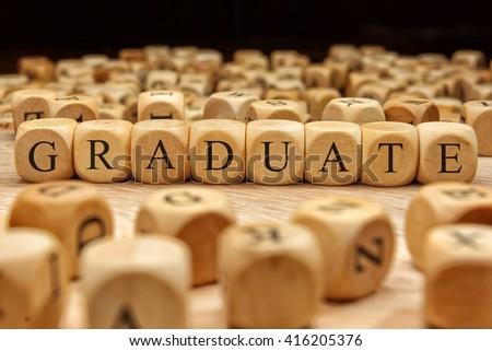 GRADUATE word written on wood block - stock photo
