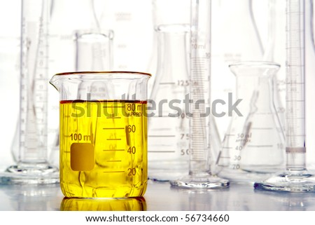 Graduated beaker filled with yellow liquid and laboratory glassware for an experiment in a science research lab - stock photo