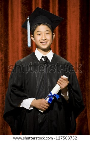 Graduated boy with mortarboard and diploma - stock photo