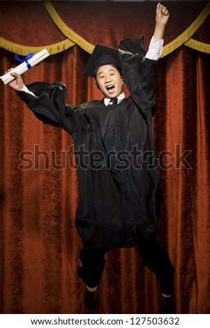 Graduated boy with mortarboard and diploma and cheering - stock photo