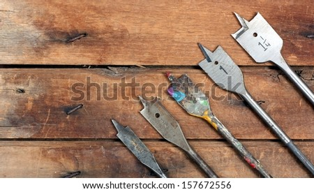 Graduated Size Spade Drill Bits on a Wood Workbench - stock photo