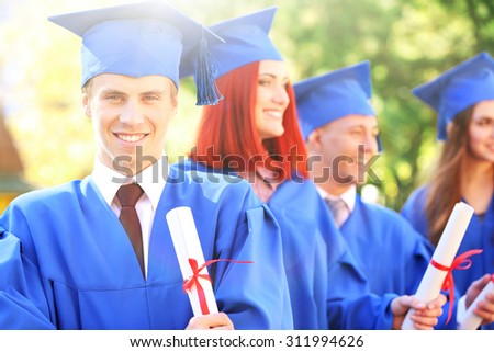 Graduated students in graduation hats and gowns, outdoors - stock photo