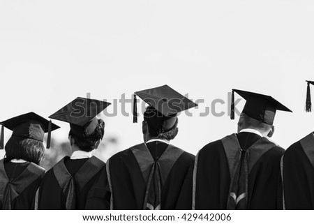 Graduates , Graduates are stand up in line to get your degree ,monochrome , Graduates stand up , Graduates people , Graduates cap,Graduates group,Graduates man ,  Graduates women , Graduates campus - stock photo