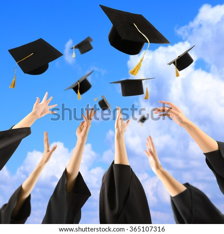 Graduates hands throwing graduation hats in the sky