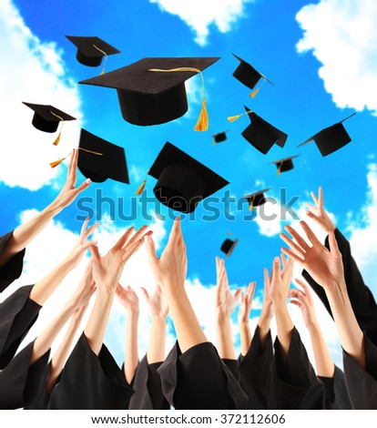 Graduates hands throwing graduation hats in the sky - stock photo