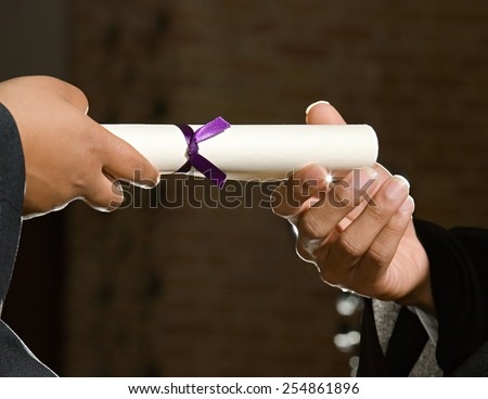 graduates holding diploma - stock photo