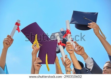 graduates stutents  throwing graduation hats in the air.