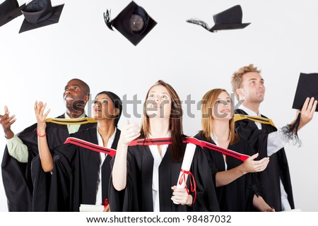 graduates throwing caps at graduation - stock photo