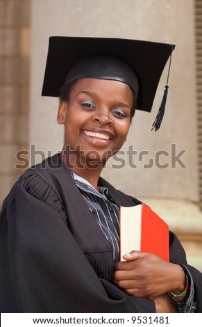 Graduating African American college student on campus with book and mortar board - stock photo