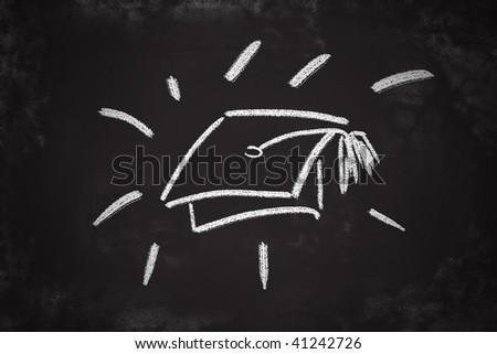 Graduation cap chalk drawing on classroom blackboard. - stock photo