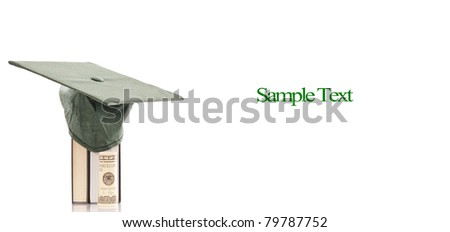 Graduation Cap on Books with Roll of Money - stock photo