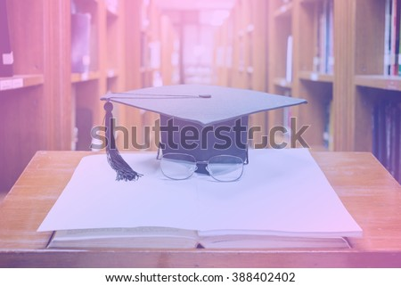graduation cap with glasses on open book,Education concept,pastel tone - stock photo