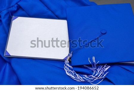Graduation Day. Cap, gown and blank diploma with copy space for personalized text or message.  - stock photo