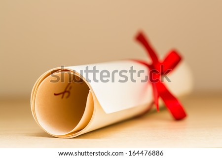 Graduation Diploma With Red Ribbon - stock photo