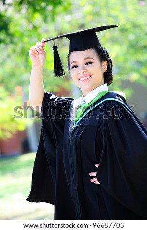 graduation female with happy face. portrait in outdoor-park. - stock photo