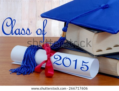Graduation image of stacked books, diploma tied with red ribbon and blue graduation cap with tassel on wooden table. Class of 2015 message. Wood panel background. Books are very thick and seem old - stock photo