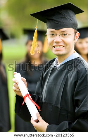 graduation man portrait smiling and looking happy outdoors - stock photo