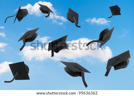 Graduation mortar boards thrown into a blue sky - stock photo