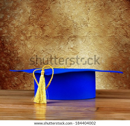Graduation mortarboard on wooden table on background of vintage wall - stock photo