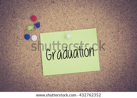 Graduation written on sticky note pinned on pinboard - stock photo