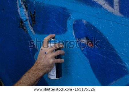 Graffiti artist holding a spray paint can to a wall - stock photo
