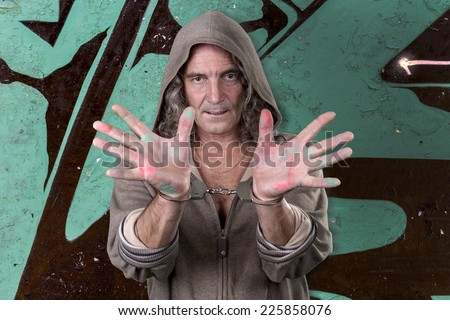 Graffiti artist in a gray dress with a hood spray paint for a picture on the wall of the urban culture. Beautiful street art graffiti. Urban Contemporary Culture. Isolated on white background - stock photo