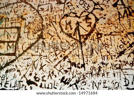 Graffiti hearts and names scratched in rusty metal