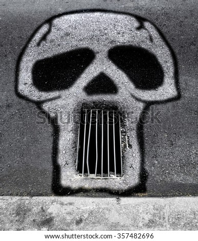 Graffiti of a skull on a asphalt road with drain cover grill as mouth for the concept of risk for bicyclist on a badly covered manhole. - stock photo
