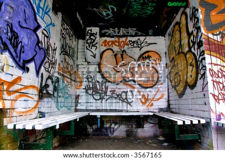 Graffiti on the walls surrounding a seating area. - stock photo