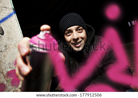 Graffiti painter drawing a picture on the wall. - stock photo
