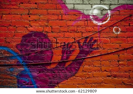 Graffiti wall in urban centers depicts a kid and bubbles with arms raised upwards in purple on a bright orange wall with ridges and black telephone wires running across the breadth of the shot - stock photo