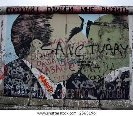 Grafitti on the Berlin Wall in Berlin, Germany. The famous kiss - stock photo
