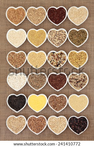 Grain and cereal food selection in heart shaped porcelain bowls over hessian background. - stock photo