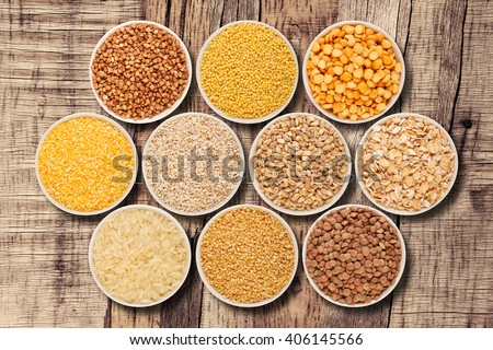 Grain and cereal food selection in porcelain bowls on wooden table, top view - stock photo