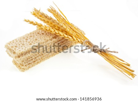 Grain bread and ears of wheat on a white background