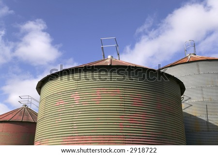 Grain drying silo's against a blue sky - stock photo