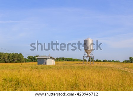 Grain Silo and Keep Shack: A missile or rocket shaped stainless steel grain silo near a keep shack in a field near Demopolis, Alabama against a blue sky.