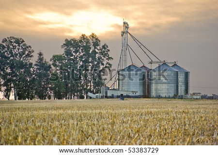 Grain silos and cropped wheat field under a cloudy sunset - stock photo