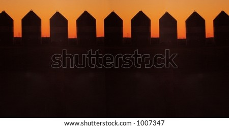 grain silos in silhouette - stock photo