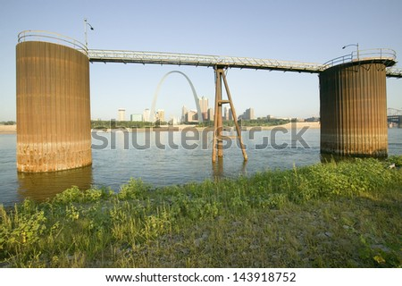 Grain site for barges and skyline of St. Louis, Missouri at sunrise from East St. Louis, Illinois on the Mississippi River - stock photo