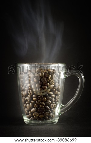 Grains of black roasted coffee in transparent cup with steam on black background