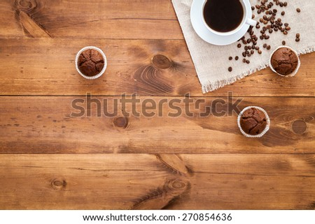Grains of coffee. Table. Scattered grains of coffee on the table top view.  Coffee mug on a napkin with cupcakes. For registration booklets and advertising of coffee. For coffee lovers - stock photo