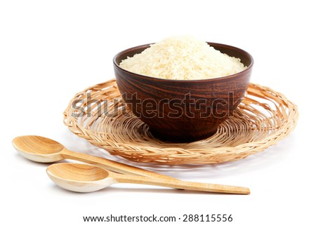 Grains of rice in a bowl and wooden spoon isolated on white background. - stock photo