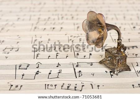 Gramophone on old sheet music - retro art background - stock photo