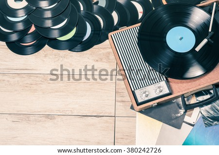 Gramophone with a vinyl records on wooden table, top view and copy space,photo desaturate and split toning for old style. - stock photo