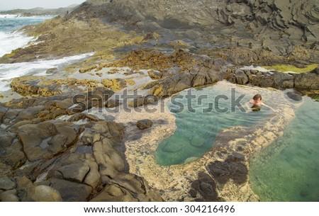 Gran Canaria, Banaderos area, naturist is bathing  in rock pools - stock photo