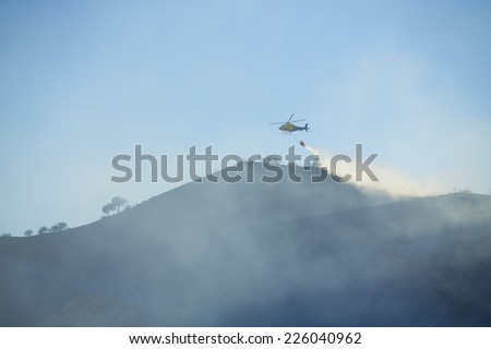 GRANADA, AUGUST 28: Fire fighting Helicopter, with bambi basket, during a fire fighting in the bush. August 28, 2014, Granada, Spain.
