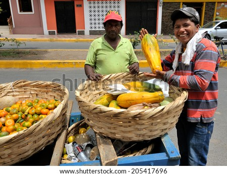 GRANADA-MARCH 19: Fruit street vendors with his mobile stand on March 19, 2014 in Granada, Nicaragua. Textiles and agriculture combined account for nearly 50% of Nicaragua's exports.  - stock photo